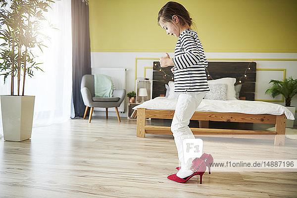 Kleines Mädchen  das sich verkleidet und rote Stöckelschuhe der Mutter trägt