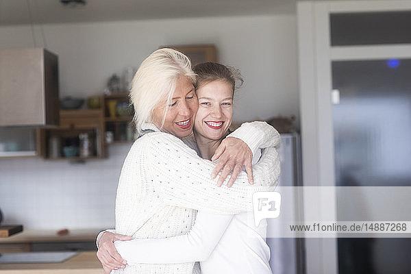 Porträt einer glücklichen Mutter  die ihre erwachsene Tochter zu Hause umarmt