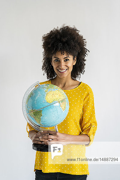 Beautiful woman holding globe  planning vacations