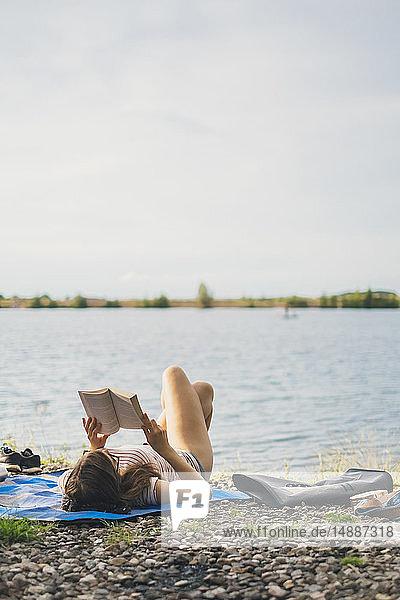 Junge Frau liegt auf einer Decke am Seeufer und liest ein Buch