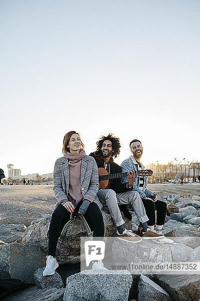 Drei glückliche Freunde mit Gitarre sitzen bei Sonnenuntergang im Freien