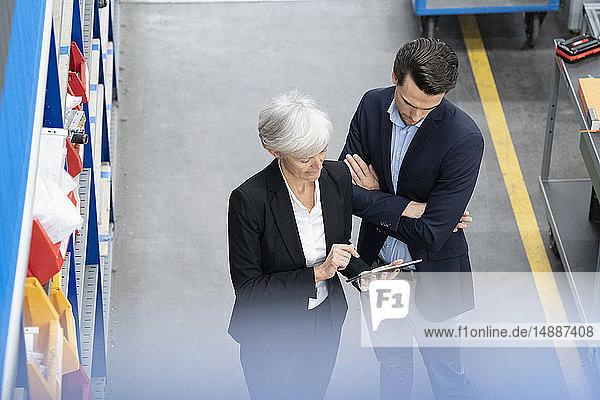 Geschäftsmann und leitende Geschäftsfrau mit Tablette in einer Fabrik