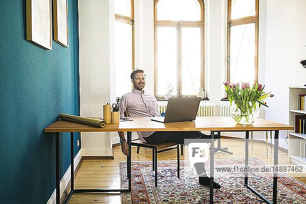 Porträt eines glücklichen entspannten Geschäftsmannes im Home Office