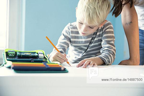 Junge macht Hausaufgaben  Mutter lehnt am Schreibtisch