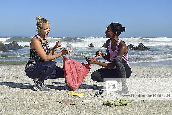 Zwei Frauen reinigen den Strand von Plastikmüll