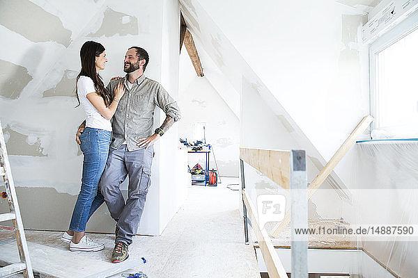 Lächelndes Paar steht auf dem Dachboden und muss renoviert werden