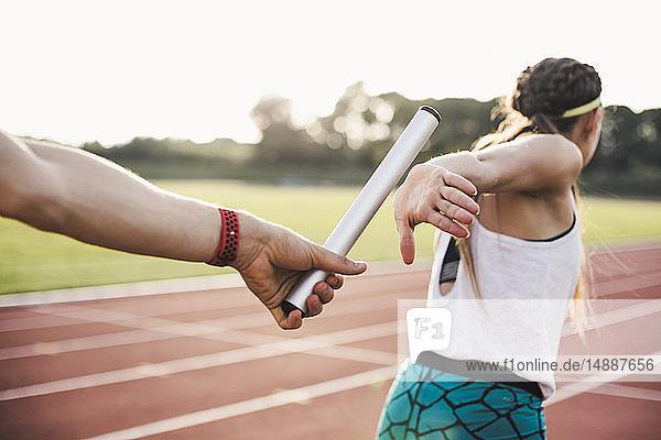 Nahaufnahme eines Athleten  der den Staffelstab an eine Athletin übergibt
