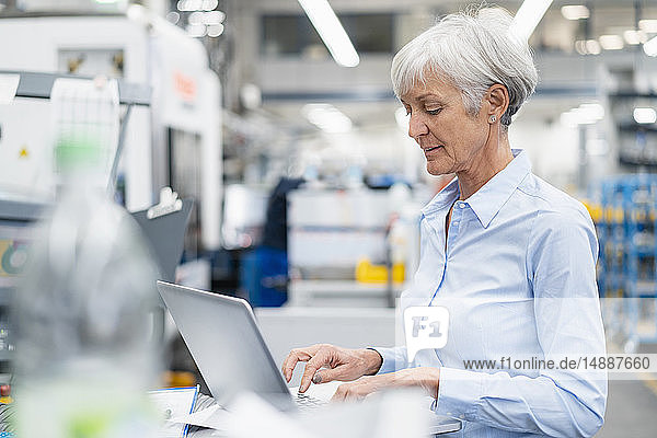 Senior businesswoman using laptop in a factory