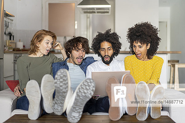 Friends sitting on couch  watching laptop