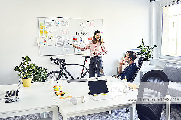 Two colleagues discussing at whiteboard in office