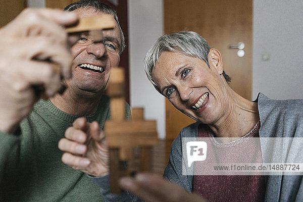 Glückliches Seniorenpaar beim Geschicklichkeitsspiel zu Hause