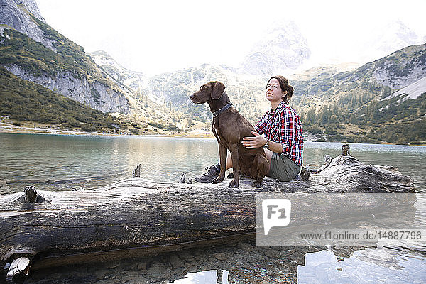 Austria  Tyrol  woman with dog sitting on tree trunk at lake Seebensee