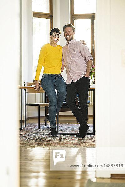 Porträt eines glücklichen Paares bei Tisch in stilvoller Wohnung