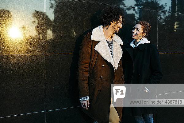Paar an einer schwarzen Wand mit miteinander sprechenden Reflexionen