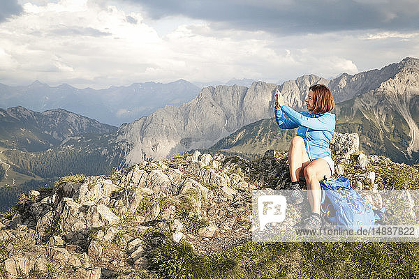 Austria  Tyrol  woman on a hiking trip in the mountains taking cell phone picture on peak