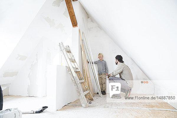 Vater und Sohn planen Dachbodenausbau