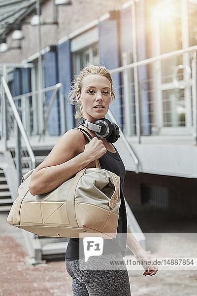 Porträt einer blonden jungen Frau mit Kopfhörer und Sporttasche vor der Turnhalle