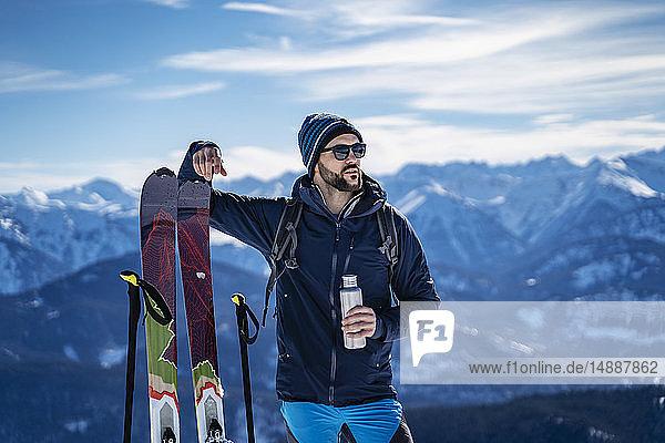 Deutschland  Bayern  Brauneck  Mann auf einer Skitour im Winter in den Bergen bei einer Pause