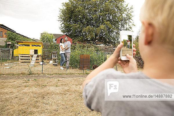 Junge macht Handyfoto von Eltern  die im Hühnerstall im Garten stehen
