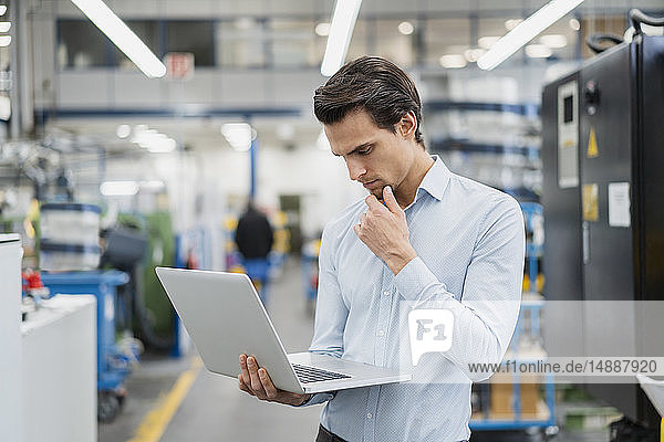 Portrait of businessman using laptop in a factory