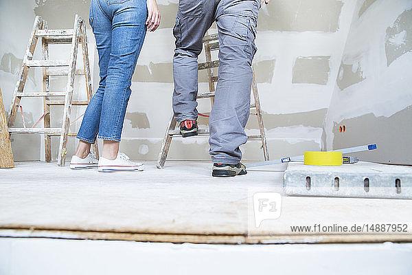 Beine eines Paares mit Leiter im Dachgeschoss  das renoviert werden soll