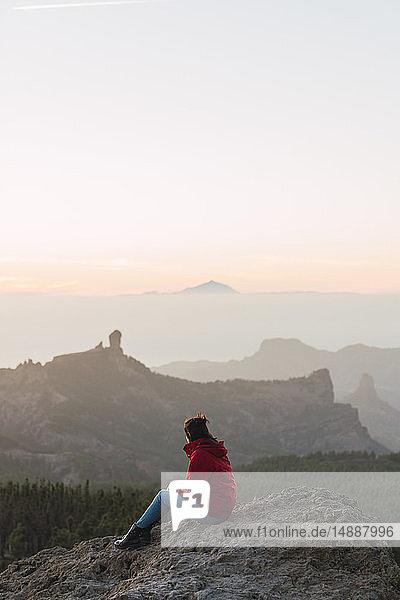 Spain  Gran Canaria  Pico de las Nieves  woman sitting on rock looking at view