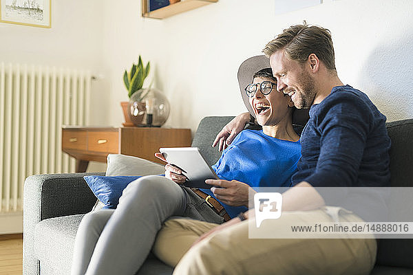 Happy casual couple relaxing on couch using tablet and laughing