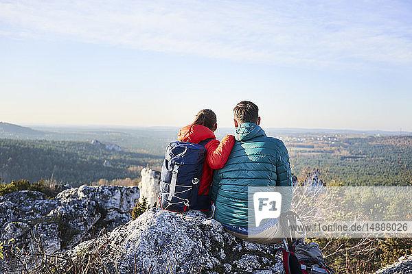 Ein Paar sitzt auf einem Felsen und geniesst die Aussicht bei einer Wanderung in den Bergen