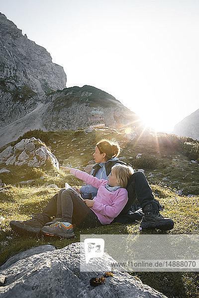 Österreich  Tirol  Mutter mit Tochter bei Sonnenuntergang in Berglandschaft ruhend