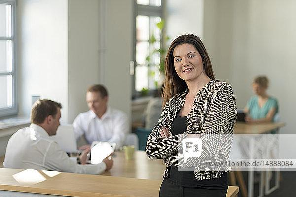Porträt einer lächelnden Geschäftsfrau im Büro mit Kollegen im Hintergrund