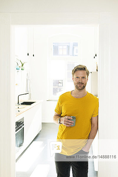 Confident casual man with coffee mug leaning against door case