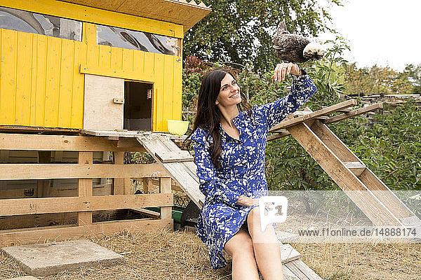 Lächelnde Frau mit polnischem Huhn im Hühnerstall im Garten