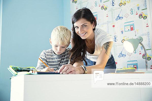 Porträt einer lächelnden Mutter  die ihrem Sohn bei den Hausaufgaben am Schreibtisch hilft