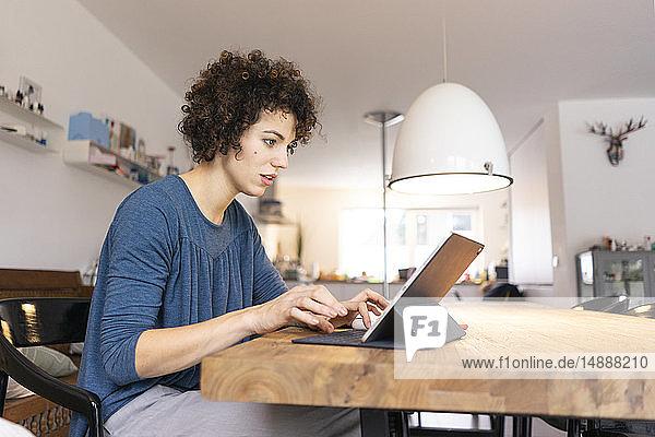 Junge Frau sitzt am Tisch und benutzt ein digitales Tablett