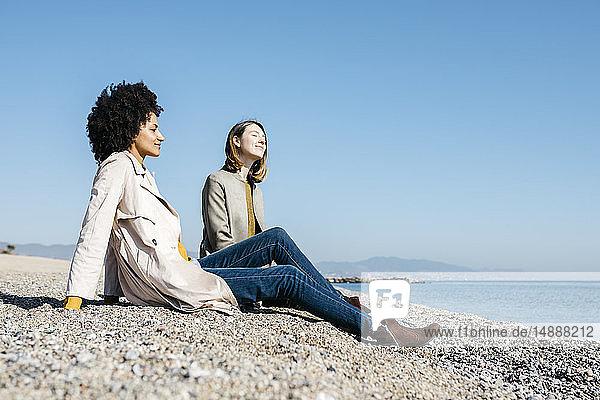Zwei Freunde sitzen am Strand und genießen ihre Freizeit