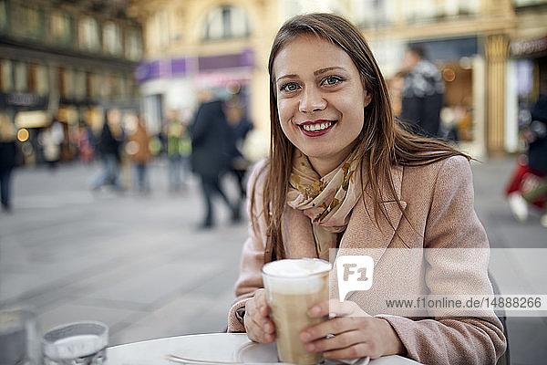 Österreich  Wien  Porträt einer lächelnden jungen Frau  die im Straßencafé Kaffee trinkt