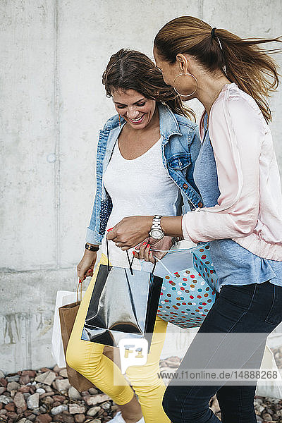 Two happy friends with shopping bags