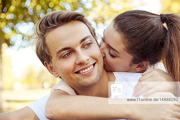 Glückliches verliebtes junges Paar küsst sich in einem Park
