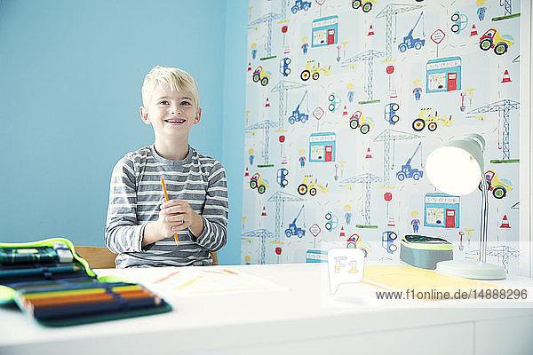 Lächelnder Junge macht Hausaufgaben am Schreibtisch im Kinderzimmer