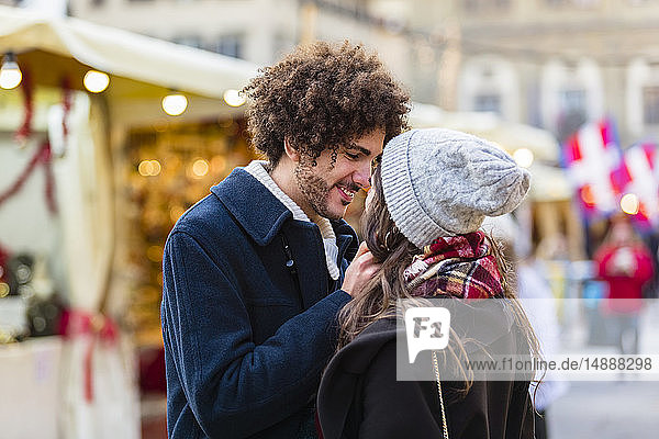 Happy affectionate young couple at Christmas market