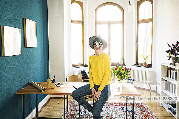 Portrait of smiling businesswoman in home office sitting on table