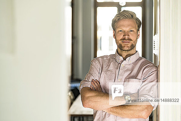 Portrait of confident casual man leaning against door case at home