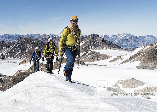 Grönland  Sermersooq  Kulusuk  Schweizer Alpen  Bergsteiger beim Wandern in verschneiter Berglandschaft
