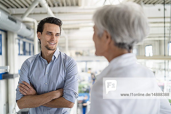 Smiling businessman talking to senior businesswoman in a factory