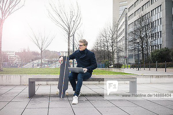 Young businessman with skateboard and laptopsitting on bench in the city