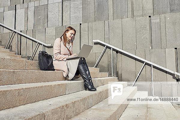 Österreich  Wien  lächelnde junge Frau sitzt mit Laptop auf der Treppe im MuseumsQuartier
