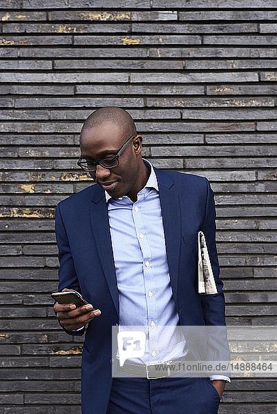 Porträt eines lächelnden Geschäftsmannes mit Zeitung  Brille und blauem Anzug  der auf sein Mobiltelefon schaut