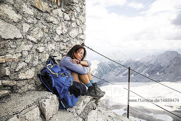 Österreich  Tirol  Frau auf Wanderung  die sich mit geschlossenen Augen auf einer Berghütte ausruht