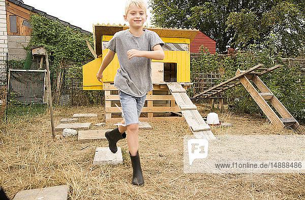 Porträt eines glücklichen Jungen  der im Hühnerstall im Garten läuft
