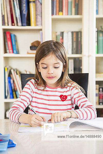 Portrait of little girl doing homework